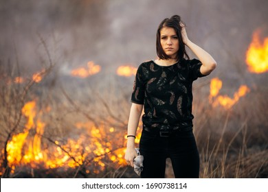 Riots, aggression, violence, arson, mayhem,protest concept.Disaster in bush forest with fire spreading in dry woods caused by pyromaniac.Vandal makes fire.Grain added,toned image