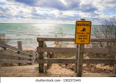 Rip Current Warning. Sign at beach entrance warning of dangerous rip currents as waves crash on to the coast of Lake Michigan.