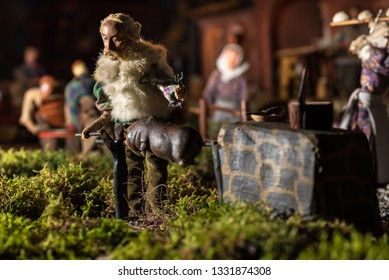Riparbella Toscany Italy, December 2018. Miniature figurines of a peasant roasting a pig with people on background