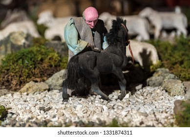 Riparbella Toscany Italy, December 2018. Miniature figurines of a peasant brushing a black horse