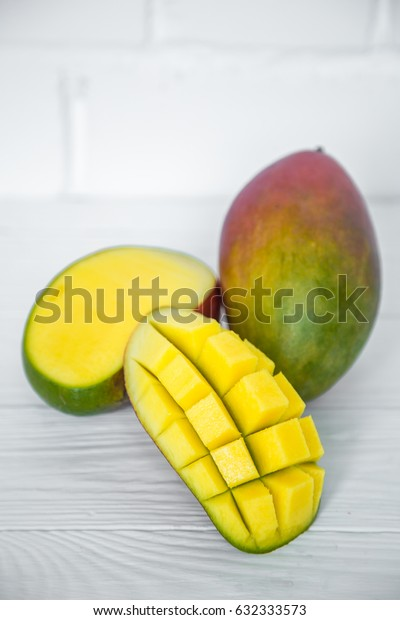 Ripe appetizing Mango with a slice cut to cubes, on white wooden background,concept of exotic fruits
