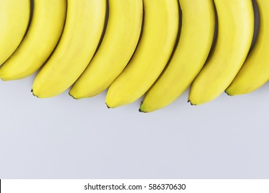 Ripe, appetizing, wholesome bananas, neatly lined in a row on a light background. The view from the top. Healthy eating