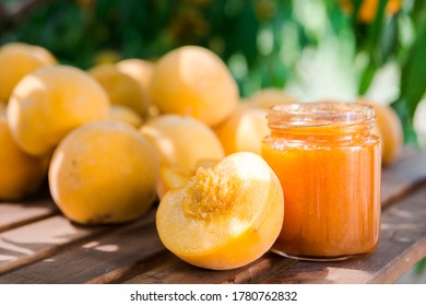 ripe appetizing yellow peaches and marmalade on table in garden