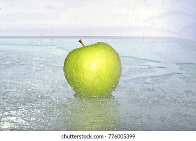 ripe apple in drops of water falling on a white background.