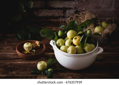 Ripe apples in a ceramic dish. Background brick, style loft. On a table foliage.
