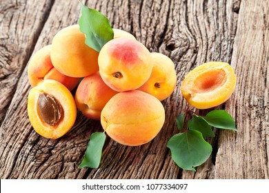 Ripe apricots and apricot leaves on the wooden background.