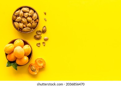 Ripe apricots in bowl with apricot kernel, top view