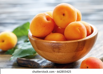Ripe apricots in a bowl on wooden table, selective focus.