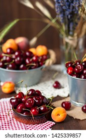 Ripe apricots and cherries in metal bowls and clay brown plate. Vintage napkins as decor. Dacha style, countryside, cozy and cute, grandmother's kitchen. Dry flowers in vase on background