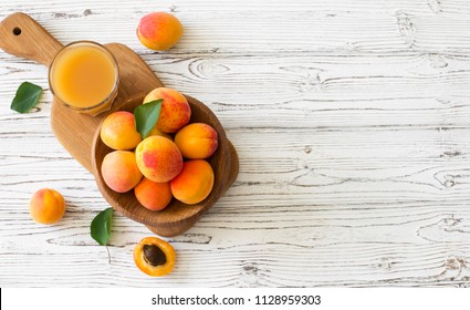 Ripe apricots and glass of juice  in wooden bowl on white wood background. Flat lay. Copy space