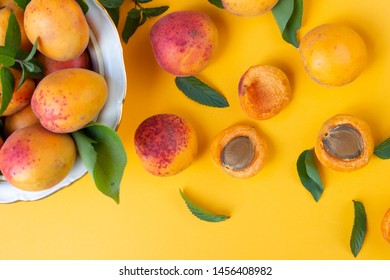 ripe apricots on orange table with leaves