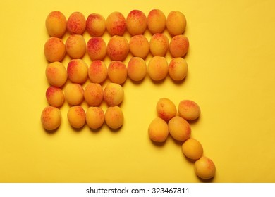 Ripe apricots on yellow surface background