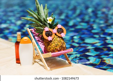 Ripe attractive girl-pineapple lying on sun chair near the turquoise swimming pool. Relaxing. Wearing funny sunglasses. Tropical summer vacation concept. Sunbathing using sunscreen lotion. Sun protect