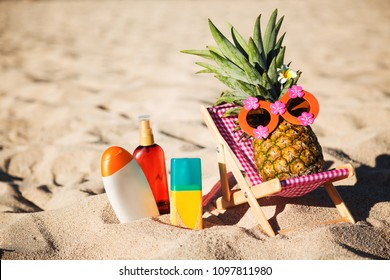 Ripe attractive girl-pineapple lying on sun chair on the sand against turquoise sea. Relaxing. Wearing funny sunglass. Tropical summer vacation concept. Sunbathing using sunscreen lotion. Sun protect