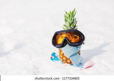 Ripe attractive pineapple in ski goggles on the snow in the mountain. Winter snowboard holidays concept. Wearing stylish warm scarf. Sunny day in the mountain. Mountain ski outfit. Snowboarder