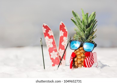 Ripe attractive pineapple in stylish mirrored sunglasses on the snow in the mountain. Winter ski holidays concept. Wearing stylish mittens, sunglass. Sunny day in the mountain. Mountain skiing outfit