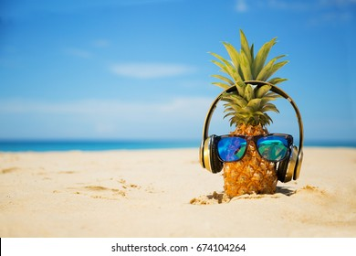 Ripe attractive pineapple in stylish mirrored sunglasses and gold headphones on sand against turquoise  sea water. Tropical summer vacation concept. Summer sunny day on the beach of tropical island