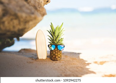 Ripe attractive pineapple surfer in stylish mirrored sunglasses with surfbord on sand against turquoise sea water. Tropical summer vacation concept. Summer sunny day on the beach of tropical island