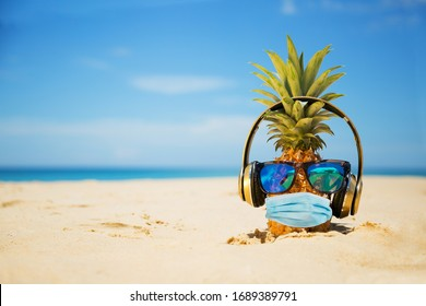 Ripe attractive pineapple wearing face mask because of Air pollution or virus epidemic in the world.  On the sand against turquoise sea. Summer vacation concept during an epidemic. New reality