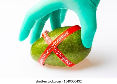 Ripe avocado entwined with ribbon with text Listeria monocytogenes . Consumer safety concept.