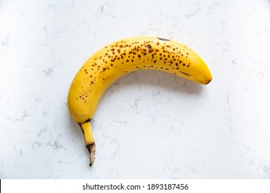 Ripe banana on a marble kitchen counter. - Shutterstock ID 1893187456