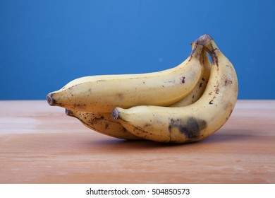 Ripe banana on wooden table  and blue background