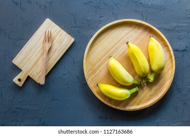 Ripe Bananas in wooden plate on black wall background.