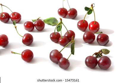 Ripe berries of a cherry of red color and their shadow on light background.