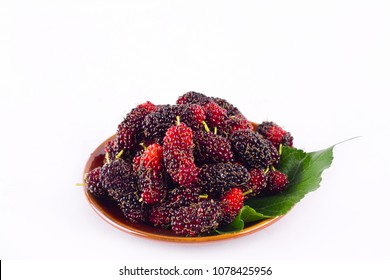 ripe berry fruit and mulberry leaf  in brown bowl on white background healthy mulberry fruit food isolated