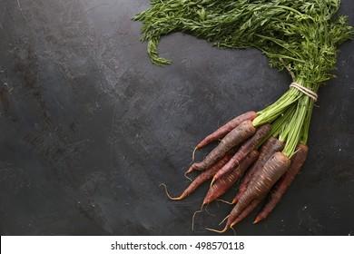 Ripe black carrots. Dark stone background. Autumn harvest.