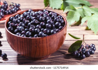 Ripe black chokeberry  in bowl and branch of aronia  on rustic wooden background