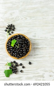 Ripe black currant in a wooden bowl on white shabby wooden table. Top view  space for text.