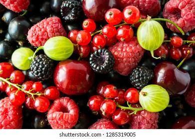 Ripe blackberries, blackcurrants, cherries, red currants, raspberries and gooseberries. Mix berries and fruits. Top view. Background berries and fruits. Various fresh summer fruits.