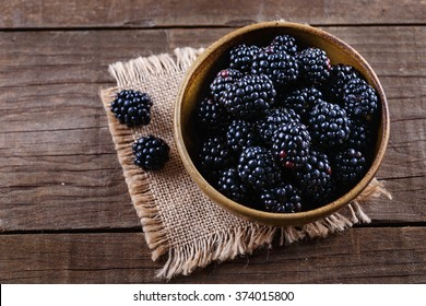 Ripe blackberries in a ceramic bowl on burlap cloth over wooden background close up. Rustic style, Selective focus