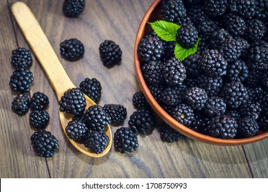 Ripe blackberries with leaves in a clay bowl on a light wooden background. Flat lay, top view. Photo of blackberry in clay bowl on wooden table. High resolution product.