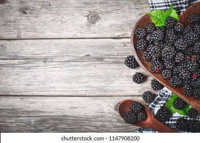 Ripe blackberry and blackberry jam on a wooden table. Top view.