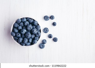 Ripe bluberries in bowl on white wooden table. Top view.