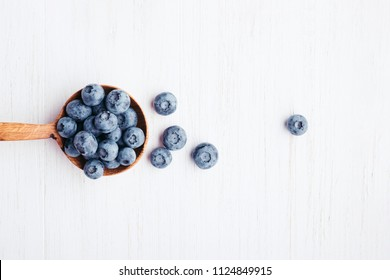 Ripe bluberries in wooden spoon on white wooden table. Top view.