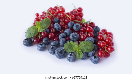 Ripe blueberries and red currants with mint. Berries at border of image with copy space for text. Background berries. Various fresh summer berries on white background.