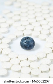Ripe blueberries surrounded by pills on all sides. Concept: natural vitamins. Close up.