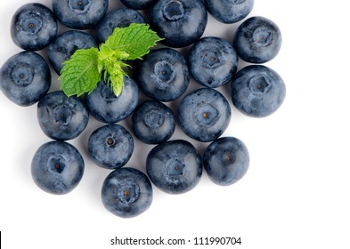 Ripe blueberry with mint closeup on white background.