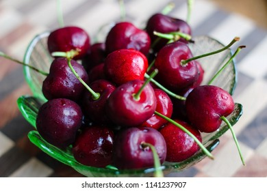 Ripe bowl of red stemmed cherries in a green dish