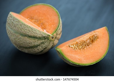 Ripe cantaloupe melon on black wooden boards