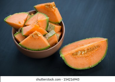 Ripe cantaloupe melon over dark wooden background