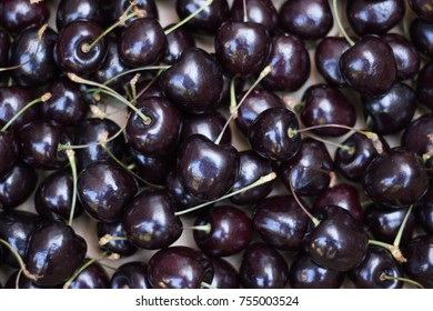 A lot of ripe cherries with cuttings lie on a table. View from above. Concept: healthy organic food. If you eat sweet cherry berry- you do not have the beriberi!