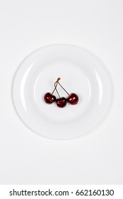 Ripe cherries on white plate on wooden background. Red sweet cherries.