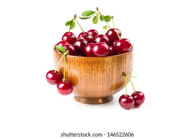 Ripe cherries in a wooden bowl isolated on white background