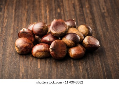 Ripe chestnuts in a frying pan on old wooden table close up with copy space.