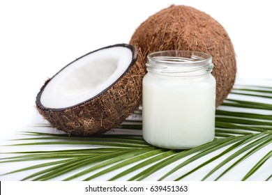 ripe coconuts and organic coconut oil in glass jar on coconut leaf isolated on white