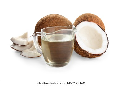 Ripe coconuts and pitcher with natural organic oil on white background